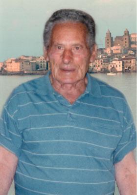 Un ritratto di Gianni Cefalù con nello sfondo il quadro di Cefalù