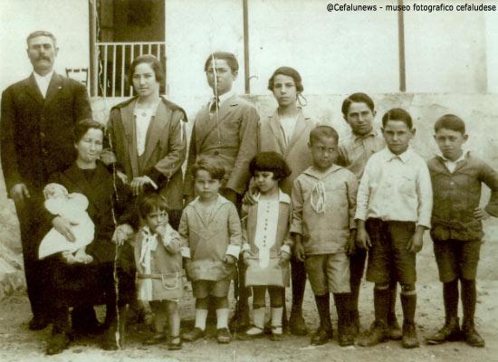 """1926 Piazza F. Crispi """"bastiuni"""" papà Salvatore Aquia e mamma Rosa con 11 figli davanti l'uscio di casa. Altri due figli nasceranno negli anni successivi"""